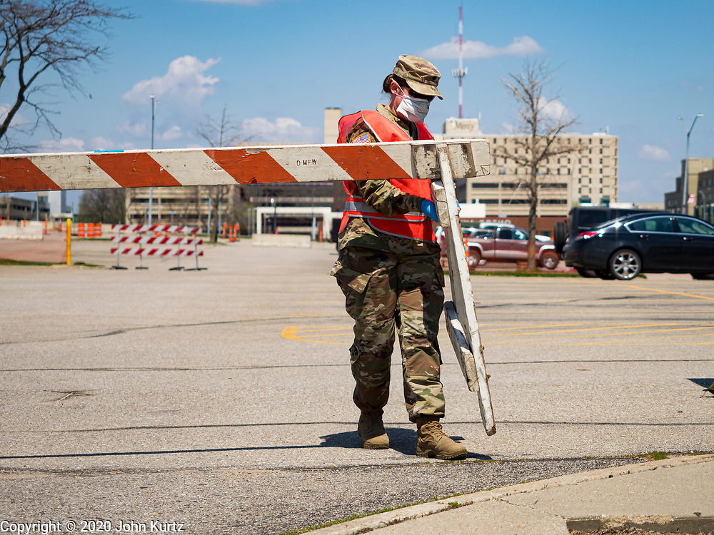 """26 APRIL 2020 - DES MOINES, IOWA: A soldier with the Iowa Army National Guard closes a gate to the COVID-19 drive through testing site in Des Moines. Iowa started mass testing Saturday, with a drive through testing site in a parking lot in downtown Des Moines. The testing this weekend is considered a """"soft opening"""" for the program and tests were reserved for medical professionals and first responders. Despite numerous outbreaks in meat packing plants throughout Iowa, members of the public have not been able to get tested. On Saturday, 25 April, there were 5,092 confirmed cases of COVID-19 (Coronavirus / SARS-CoV-2) in Iowa (an increase of 647 since Friday, April 24) and 112 deaths in Iowa caused by COVID-19.           PHOTO BY JACK KURTZ"""