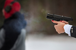 A member of Hillary Clinton's security detail takes part in training drills by firing a weapon at a training facility in Summit Point, W.Va on Dec. 17, 2011.