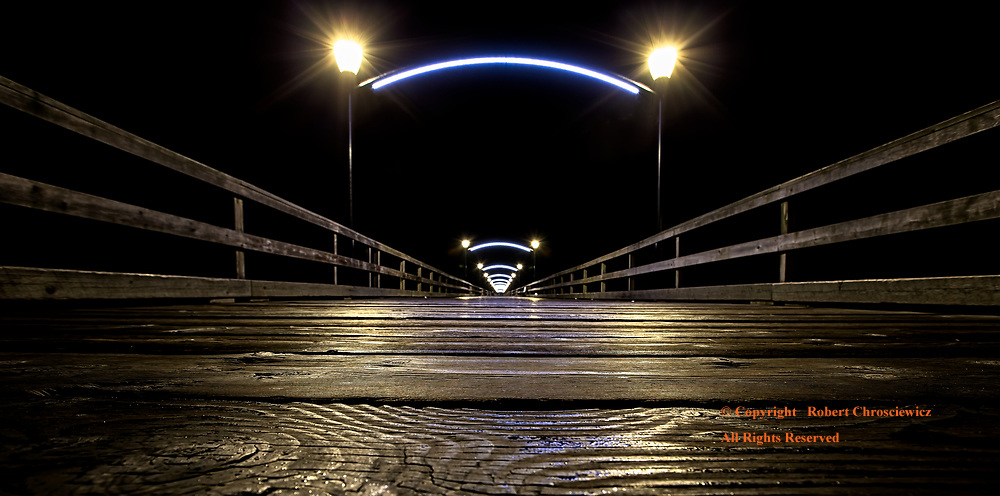 Boardwalk Low Down: The eye is guided from this low angled view, down the parallel guard rails of an illuminated wooden pier in White Rock, Surrey British Columbia Canada.