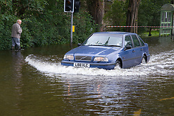 Car drives through flooded street after torrential rain caused flooding in Oxford and the Thames Valley area; July 2007,