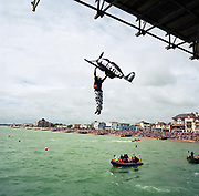 A competitor in the annual Birdman of Bognor event attempts to fly at Bognor Regis, East Sussex, England. English eccentrics gather annually at the southern seaside town to jump from the pier into the chilly waters of the English Channel. Fun jumpers 'wearing' their aeroplane suits compete for a £25,000 prize for the one to fly 100 metres from the pier platform – a record not yet achieved. Entrants (who often jump for charity rather than any aeronautical pretensions) include sugar plum fairies, condoms, Ninja Turtles and vampires. The winner was a hang-glider pilot reaching 26 metres but here, a Spitfire sponsored by a milk company drops vertically. Picture from the 'Plane Pictures' project, a celebration of aviation aesthetics and flying culture, 100 years after the Wright brothers first 12 seconds/120 feet powered flight at Kitty Hawk,1903.