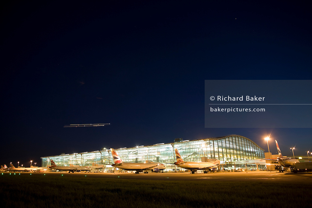 "With faint traces of an evening metor shower in the sky, a wide exterior view of Heathrow Airport's Terminal 5 building in West London. Created by the Richard Rogers Partnership (now Rogers Stirk Harbour and Partners). As the last light of the day fades and a departing aircraft's lights streak across the sky, the brightness of terminal lights shine through massive panes of window glass. At a cost of £4.3 billion, the 400m long T5 is the largest free-standing building in the UK with the capacity to serve around 30 million passengers a year. The Terminal 5 public inquiry was the longest in UK history, lasting four years from 1995 to 1999. From writer Alain de Botton's book project ""A Week at the Airport: A Heathrow Diary"" (2009). ......"