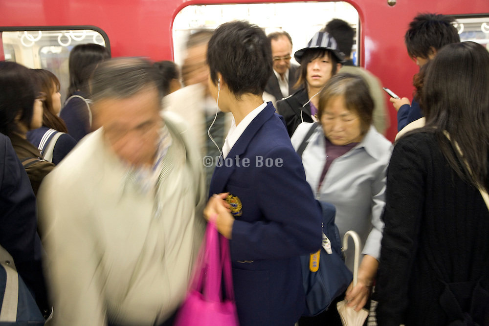 commuters exiting and entering a train during evening rush Tokyo Japan