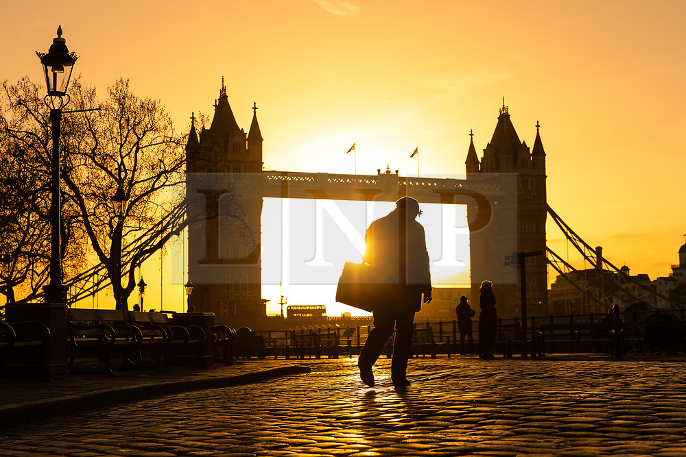 © Licensed to London News Pictures. 22/12/2018. London, UK.  A person walks along the Thames path in front of Tower Bridge shortly after sunrise, as the capital is experiencing milder and sunny weather this morning.  Photo credit: Vickie Flores/LNP