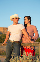 hot cowboy leaning against a fence with a beautiful girl at sunset