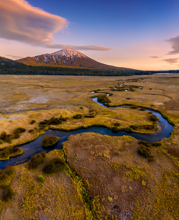 A drone's eye view over Sparks Meadow at sunset shows the meandering waters of Fall Creek with Mount Bachelor in the background.