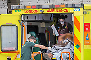 An ambulance crew in some protective clothing unloads a patient at A&E - The vital work of the NHS continues at St Thomas' Hospital - The 'lockdown' continues for the Coronavirus (Covid 19) outbreak in London.