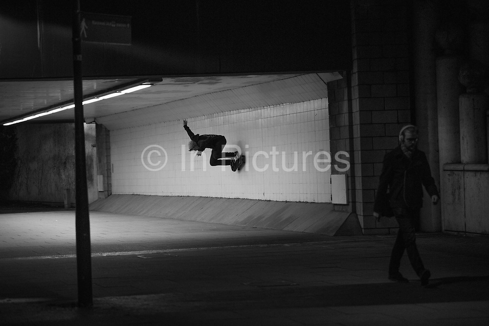 A male skateboarder performs a wall ride trick in an underpass on the 7th January 2014 in London in the United Kingdom.