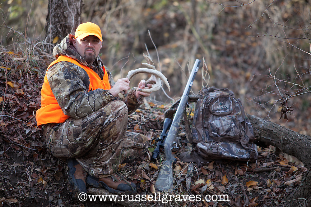 DEER HUNTER WEARING REALTREE AP CAMOUFLAGE AND BLAZE ORANGE CALLING DEER WITH RATTLING ANTLERS WHILE A THOMPSON CENTER OMEGA MUZZLELOADER LIES BESIDE HIM