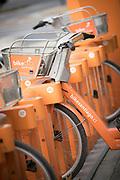 Close up of orange, rental bikes on city street, Santiago, Chile