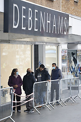 © Licensed to London News Pictures. 02/12/2020. Harrow, UK. Shoppers queue up outside a branch of Debenhams in Harrow, north London. Debenhams is set to close putting 12,000 jobs at risk. A tiered system of local lockdowns will now come into force in England with non-essential retail, gyms, hairdressers and other personal care businesses allowed to open after England's month long lockdown came to an end. Photo credit: Peter Macdiarmid/LNP