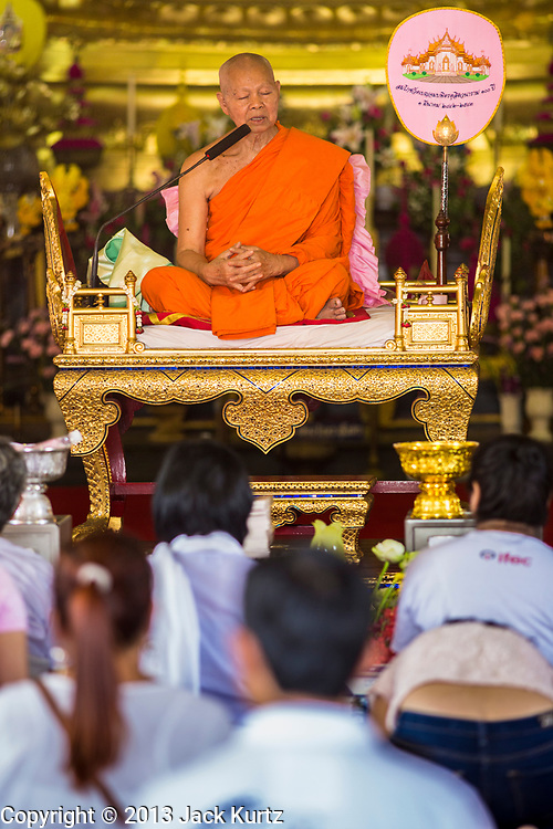 """25 FEBRUARY 2013 - BANGKOK, THAILAND:  Thai Buddhists gather in Wat Benchamabophit Dusitvanaram (popularly known as either Wat Bencha or the Marble Temple) to listen to the abbot speak on Makha Bucha Day. Makha Bucha is a Buddhist holiday celebrated in Myanmar (Burma), Thailand, Cambodia and Laos on the full moon day of the third lunar month (February 25 in 2013). The third lunar month is known in Thai is Makha. Bucha is a Thai word meaning """"to venerate"""" or """"to honor"""". Makha Bucha Day is for the veneration of Buddha and his teachings on the full moon day of the third lunar month. Makha Bucha Day marks the day that 1,250 Arahata spontaneously came to see the Buddha. The Buddha in turn laid down the principles his teachings. In Thailand, this teaching has been dubbed the 'Heart of Buddhism'.     PHOTO BY JACK KURTZ"""