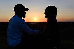 © Licensed to London News Pictures. 01/09/2018. LONDON, UK.  A couple watch the sunset on one of the manmade mounds at Northala Fields near Northolt in west London on the first day of the meteorological autumn.  The forecast is for a few more warm days before temperatures start to cool.  Photo credit: Stephen Chung/LNP