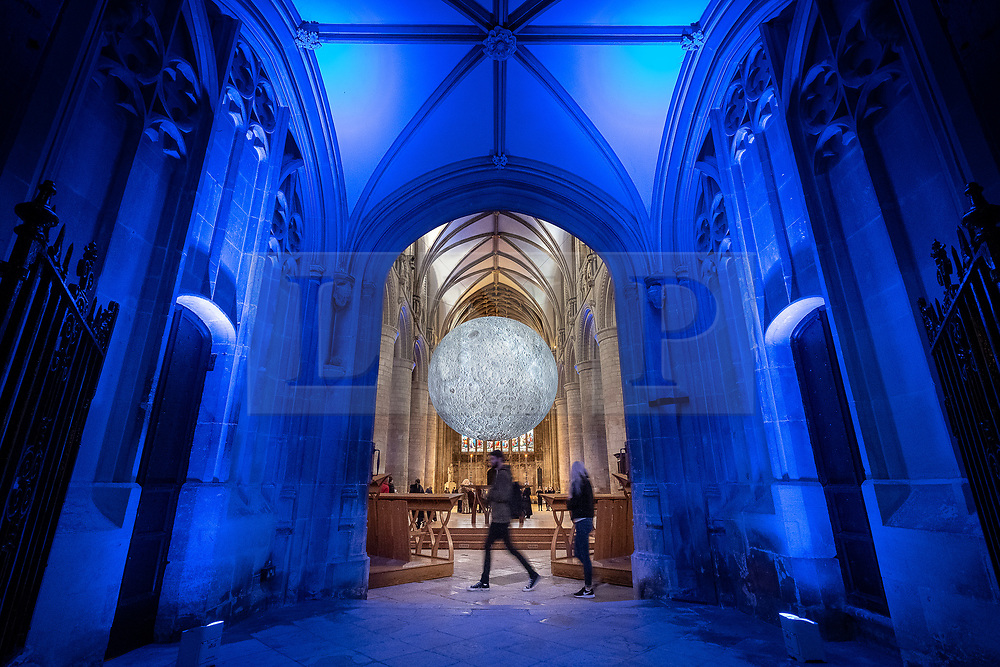 "© Licensed to London News Pictures 16/10/2019, Gloucester, UK. First day of ""The Museum of the Moon"" a touring artwork by artist Luke Jerram, displaying a 3D replica of the Moon, internally lit and floating in the Nave of Gloucester Cathedral. The lunar imagery is accompanied by immersive surround sound composed by BAFTA award winner, Dan Jones.Photo Credit : Stephen Shepherd/LNP"