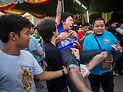 "07 MARCH 2015 - NAKHON CHAI SI, NAKHON PATHOM, THAILAND: Volunteers bring a man out of a trance after he charged the stage at the Wat Bang Phra tattoo festival. Wat Bang Phra is the best known ""Sak Yant"" tattoo temple in Thailand. It's located in Nakhon Pathom province, about 40 miles from Bangkok. The tattoos are given with hollow stainless steel needles and are thought to possess magical powers of protection. The tattoos, which are given by Buddhist monks, are popular with soldiers, policeman and gangsters, people who generally live in harm's way. The tattoo must be activated to remain powerful and the annual Wai Khru Ceremony (tattoo festival) at the temple draws thousands of devotees who come to the temple to activate or renew the tattoos. People go into trance like states and then assume the personality of their tattoo, so people with tiger tattoos assume the personality of a tiger, people with monkey tattoos take on the personality of a monkey and so on. In recent years the tattoo festival has become popular with tourists who make the trip to Nakorn Pathom province to see a side of ""exotic"" Thailand.   PHOTO BY JACK KURTZ"