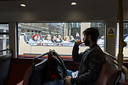 A bus passenger sits on the top deck of a double-decker bus as a tour bus busy with tourists passes-by, on 19th October 2017, in London, England.