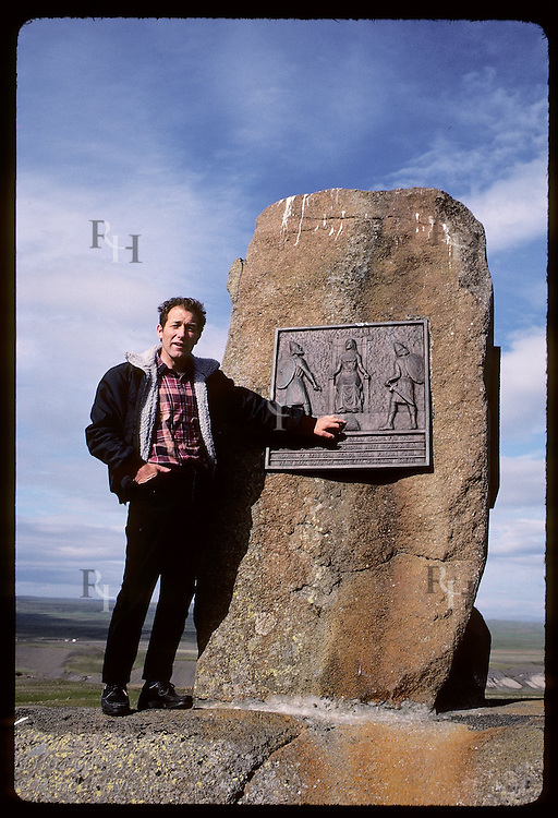 Farmer points to panel on monument to Grettir's Saga depicting delivery of Grettir's head;Bjarg Iceland
