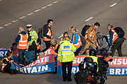 Surrey Police officers try to remove Insulate Britain climate activists, some of whom carrying power tools and other implements, from the clockwise carriageway of the M25 between Junctions 9 and 10 on 21st September 2021 in Ockham, United Kingdom. Activists briefly blocked both carriageways of the motorway as part of a campaign intended to push the UK government to make significant legislative change to start lowering emissions before they were removed and arrested by Surrey Police.