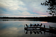 Sunset over a lake with people sitting in the Northwoods of Wisconsin