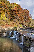 Lower Falls, in Cataract Falls State Recreation Area –  Indiana's largest-volume waterfall. Mill Creek plunges 20 feet in the set of Upper Falls, and a half a mile downstream the Lower Falls drops 18 feet, for a total drop of 86 feet including intermediate cascades. Autumn foliage colors were brilliant but water volume was low for this photo in mid October 2015. The park's limestone outcroppings formed millions of years ago when the region was covered by a large shallow ocean. Cataract Falls State Recreation Area is an hour southwest of Indianapolis, near Cloverdale, Indiana, USA.