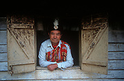 """An elderly gentleman of the indigenous Lepcha people looks through a window of his house, on 18th June 1995, in Kalimpong, West Bengal, India. The Lepcha are also called the Rongkup meaning the children of God and the Rong, Mútuncí Róngkup Rumkup """"beloved children of the Róng and of God""""), and Rongpa are among the indigenous peoples of Sikkim, India and number between 30,000 and 50,000. Many Lepcha are also found in western and southwestern Bhutan, Tibet, Darjeeling, the Mechi Zone of eastern Nepal, and in the hills of West Bengal. (Photo by Richard Baker / In Pictures via Getty Images)"""