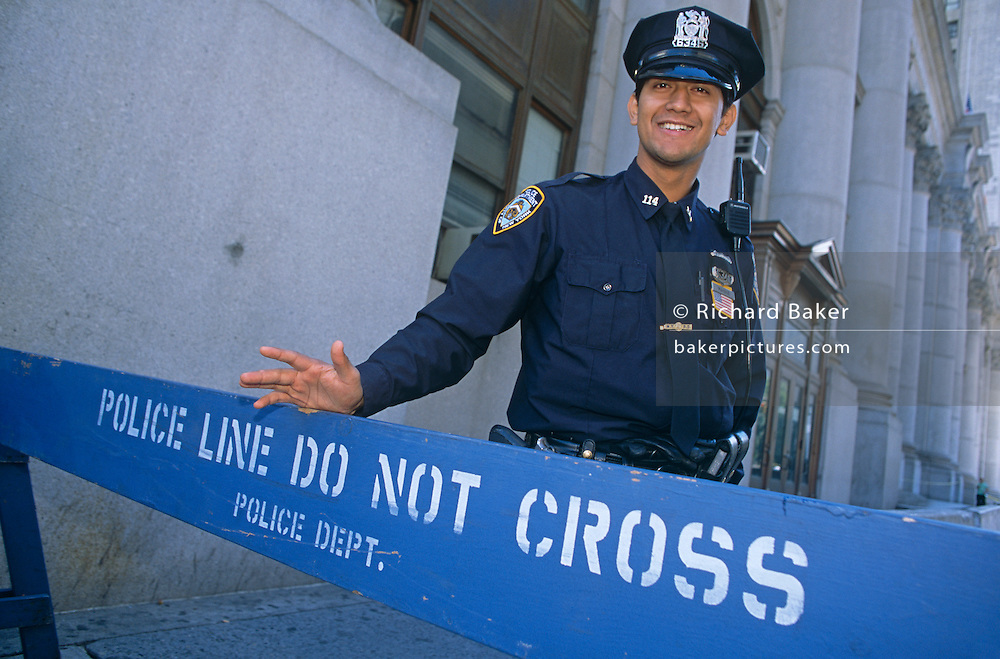 A New York City policeman (NYPD) mans a do not cross barrier, good-naturedly stopping in the week after 9/11 in Manhattan.