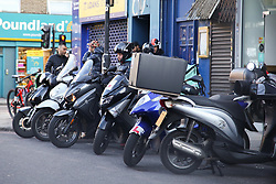 © Licensed to London News Pictures. 05/05/2020. London, UK. A number of Uber riders wait outside a restaurant in Finsbury Park, north London as there is an increase in fast food delivery due to coronavirus lockdown. Uber riders and drivers will be required to wear face covering. Photo credit: Dinendra Haria/LNP
