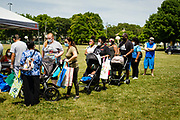"""19 JULY 2020 - DES MOINES, IOWA: People wait in line befre """"A Celebration of Black Motherhood"""" opened in Des Moines Sunday. The event was organized by the Supply Hive and Black Lives Matter. Items were donated by members of the community and redistributed to at risk families. They distributed diapers, sanitary products, clothes, books, and toys. They had enough material to help 200 families.          PHOTO BY JACK KURTZ"""