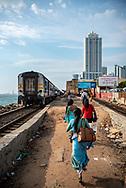 Passengers hurry to catch a train about to depart Kollupitiya Railway Station in Colombo, Sri Lanka