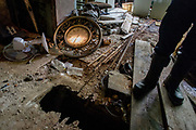 19th century derelict building ordered for demolition by Investigative Engineering Services, Assistant Commissioner Tim Lynch, Manhattan, New York City. His legs in boots are seen from waist down amid the unsafe flooring of this dangerous building. Tim works in the prevention of damage to old and ensuring new buildings are up to standard plus often, assessing the status of a collapsed structure. From the chapter entitled 'The Skyline' and from the book 'Risk Wise: Nine Everyday Adventures' by Polly Morland (Allianz, The School of Life, Profile Books, 2015).