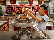 28 AUGUST 2015 - BANGKOK, THAILAND: A man makes merit by pouring oil into a lamp at Wat Mangkon Kamalawat in the Chinatown section of Bangkok on Hungry Ghost Day. Wat Mangkon Kamalawat is the largest Mahayana Buddhist temple in Chinatown. Mahayana  Buddhists believe that the gates of hell are opened on the full moon of the seventh lunar month of the Chinese calendar, and the spirits of hungry ghosts allowed to roam the earth. These ghosts need food and merit to find their way back to their own. People help by offering food, paper money, candles and flowers, making merit of their own in the process. Hungry Ghost Day is observed in communities with a large ethnic Chinese population, like Bangkok's Chinatown.ese population, like Bangkok's Chinatown.      PHOTO BY JACK KURTZ
