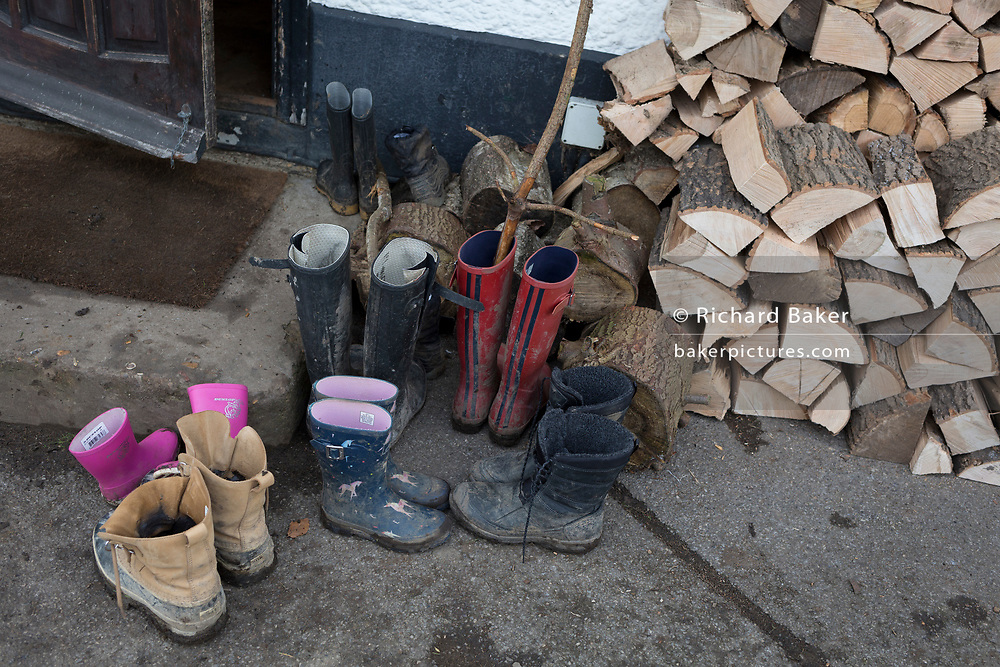 A pile of muddy woodland walkers' boots which have been left outside the Bucks Head pub in Godden Green, 5th January 2019, in Kent, England.
