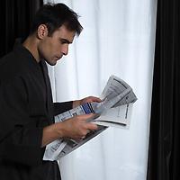 portrait of man in bathrobe reading newspaper
