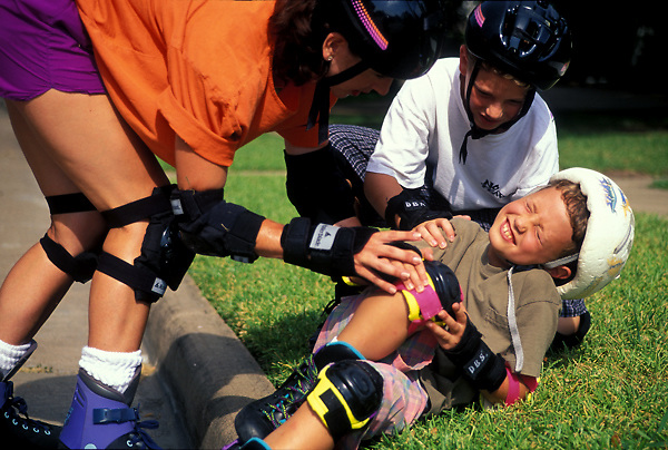 Stock photo of a woman consoling a young boy who has fallen while rollerblading.