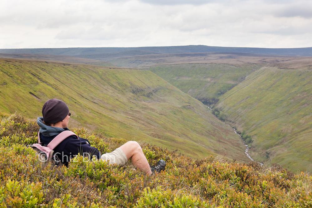 Walker taking in the view across Alport Dale, Peak District National Park.
