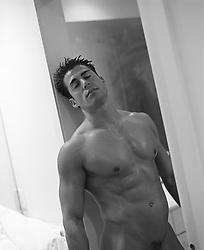 nude man resting on a doorway