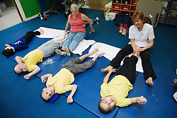 Carers at special school giving children foot massage,