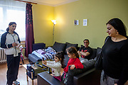 """Volunteer Jolana Smarhovycova (right) with father Eduard Polanski (47) and his daughters Kristina (taking a photograph) and Sara (6) in their temporary home in Ostrava. Sara's mother (left) was advised from one of the schools that she should not enrol her daughter there - after the girl passed the enrolment test - because Sara is so """"slim"""". Mother Ingrid Kandracova (36) new that the final decision is on her side and she refused the advice and enrolled her daughter in the school."""