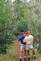 Two men reading a map while  in the wilderness of Hawaii