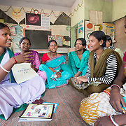 CAPTION: Sahiya Anupma Soren takes a monthly session with the 15-19-year olds. The discussion covers delaying the age of marriage, antenatal care, where the ARSH clinic is and what it does, the methods of family planning that the facility can help with, and what their respective pros and cons are. The Government requires these sessions to be conducted monthly. Sahiyas are given an incentive of ₹ 75 per session they lead. The girls are asked to come on a regular basis, as the knowledge imparted builds over time. LOCATION: Pawra Anganwadi Centre (AWC), Ghatshila (block), Purbi Singhbhum (district), Jharkhand (state), India. INDIVIDUAL(S) PHOTOGRAPHED: From left to right: Anupma Soren, Pritilata Giope, Sarshati Hansda, Maya Namata, Kajal Namata and Sunita Murmu .