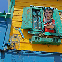 South America, Argentina, Buenos Aires. Papier Mache figure beckons from window in La Boca neighborhood.