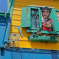 South America, Argentina, Buenos Aires. Papier Mache figure beckons from window in La Boca neighborhood.