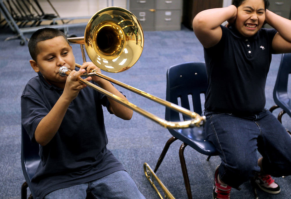 ORG XMIT: DMN1009301721565558 Tiare Chuc, right, covers her ears as Jose Alvarado plays a particularly loud F note during band director Alejandro Story's sixth grade trombone class at Daggett Middle School in Fort Worth September 30, 2010.  The Mr. Holland's Opus Foundation and Fidelity Investments recently donated a number of instruments, including the trombone Jose plays, to Daggett for its band program. (Courtney Perry/The Dallas Morning News) 10052010xMETRO
