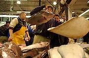 Fishmonger Warren Kremlin tosses fish at the Fulton Fish Market in Manhattan, NY. 2/7/2005