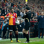 Referee's Ozgur Yankaya show the yellow card to Galatasaray's Hamit Altintop (L) during their Turkish Super League soccer match Galatasaray between Genclerbirligi at the TT Arena at Seyrantepe in Istanbul Turkey on Friday, 08 March 2013. Photo by Aykut AKICI/TURKPIX