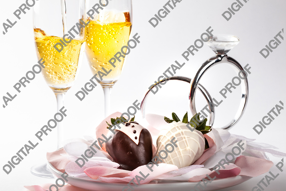 Strawberries covered in chocolate decorated as bride and groom with champagne glasses in the background