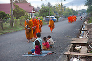 In Ban Phan Luang, across the Nam Khan River from Luang Prabang, Laos. Every morning at dawn, Buddhist monks walk down the streets collecting food alms from devout, kneeling Buddhists, and some tourists. They then return to their temples, or wats, and eat together. This procession is called Tak Bat, or Making Merit.