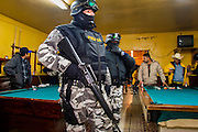 "05 FEBRUARY 2005 - NOGALES, SONORA, MEXICO: Nogales, Mexico police in a bar check customers' ID cards during an anti-gang sweep. Members of ""Grupo Operativos"" a special operations unit of the Nogales, Sonora, Mexico, police department, on patrol in Nogales, Saturday night, Feb. 5. The Operativos specialize in anti-gang enforcement and drug interdiction missions. In recent months they have stepped up patrol activity in Nogales communities near the border. In January 2005, the US Department of State has issued a travel advisory advising US citizens to avoid travel along the US Mexican border because of increased violence, including the kidnapping of US citizens, in border communities. Most of the violence has been linked to the drug cartels, who are increasingly powerful in Mexico. The Operativos also patrol the districts of Nogales frequented by US tourists in an effort to prevent crime directed against US citizens.   PHOTO BY JACK KURTZ"