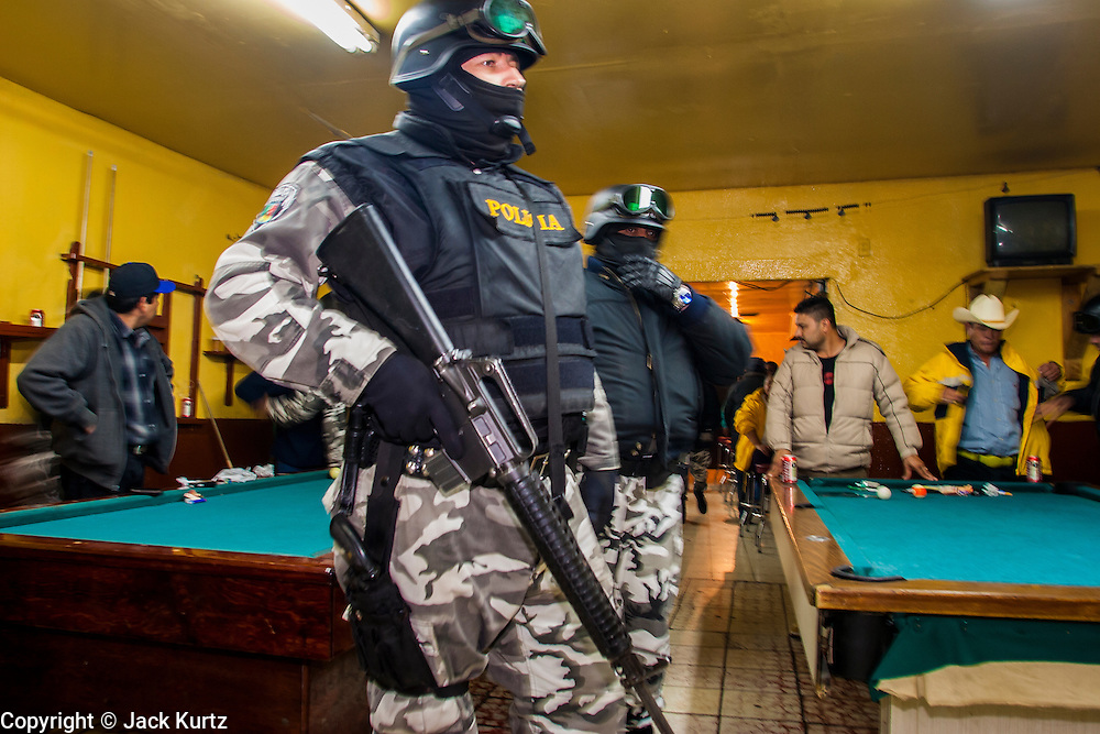 """05 FEBRUARY 2005 - NOGALES, SONORA, MEXICO: Nogales, Mexico police in a bar check customers' ID cards during an anti-gang sweep. Members of """"Grupo Operativos"""" a special operations unit of the Nogales, Sonora, Mexico, police department, on patrol in Nogales, Saturday night, Feb. 5. The Operativos specialize in anti-gang enforcement and drug interdiction missions. In recent months they have stepped up patrol activity in Nogales communities near the border. In January 2005, the US Department of State has issued a travel advisory advising US citizens to avoid travel along the US Mexican border because of increased violence, including the kidnapping of US citizens, in border communities. Most of the violence has been linked to the drug cartels, who are increasingly powerful in Mexico. The Operativos also patrol the districts of Nogales frequented by US tourists in an effort to prevent crime directed against US citizens.   PHOTO BY JACK KURTZ"""