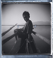 Portrait of a young Filipino boy looking at the camera with a big smile on his face while sitting on the bow of a tiny wooden boat, Palawan Island, Philippines, Southeast Asia